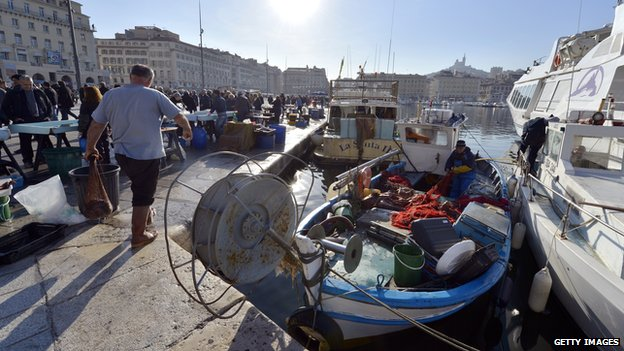 A fisherman works on his boat next to a fish market in the Vieux Port of Marseille in January 2013
