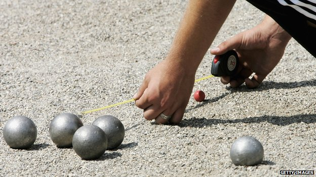 A petanque player measures the distance from a boule to the jack