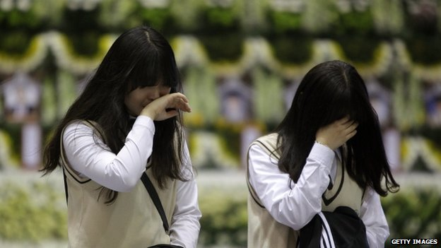 Students from Danwon high school weep after tribute at a group memorial altar for victims of sunken passengers ship at the Ansan Olympic Memorial Hall on 23 April 2014 in Ansan, South Korea