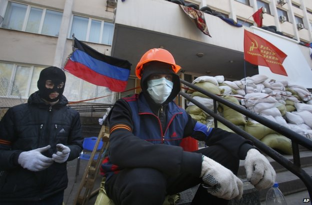 Masked pro-Russian protesters guard a barricade in front of the city hall in Mariupol, Ukraine, 17 April