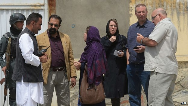Foreign nationals talk with Afghan security personnel at the gate of the Cure hospital