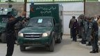 An ambulance carrying victims of the shooting leaves through the gate of the Cure hospital in Kabul