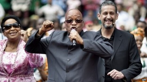 South African President Jacob Zuma (2nd L) sings and dances on the stage at the Ellis Park stadium in Johannesburg as he stands next to Bishop Marcelo Pires (2nd R) attending a Good Friday service with the Universal Church of the Kingdom of God on 18 April 2014