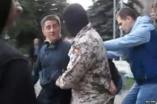 Video grab showing Volodymyr Rybak being manhandled by a masked man outside Horlivka town hall, 17 April