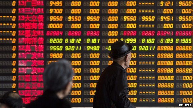 Investors look at information displayed on an electronic screen at a brokerage house in Shanghai, 14 April 2014