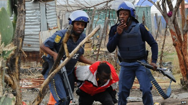 South African police arrest a miner in Marikana on 15 September 2012
