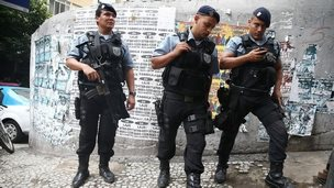 Police keep watch near the pacified Pavao-Pavaozinho community, just blocks from Copacabana Beach, on April 23, 2014