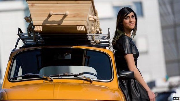 Presenter Namra Saleem with a coffin on top of her car