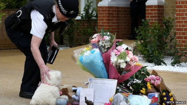 A policeman stands a teddy bear next to flowers