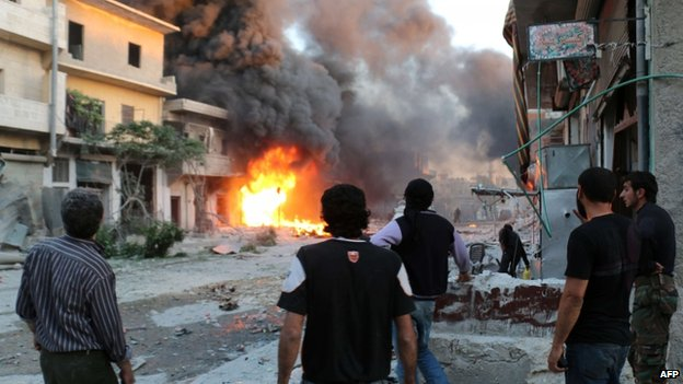 Rebel fighters and civilians stand looking at a burning building following a reported barrel bomb attack by Syrian government forces in Aleppo, 20 April 2014