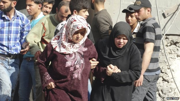 Women hold each other as they are seen at a site hit by what activists said were barrel bombs dropped by forces loyal to Syria's President Bashar al-Assad in the northern town of Atareb, in Aleppo province, 24 April 2014