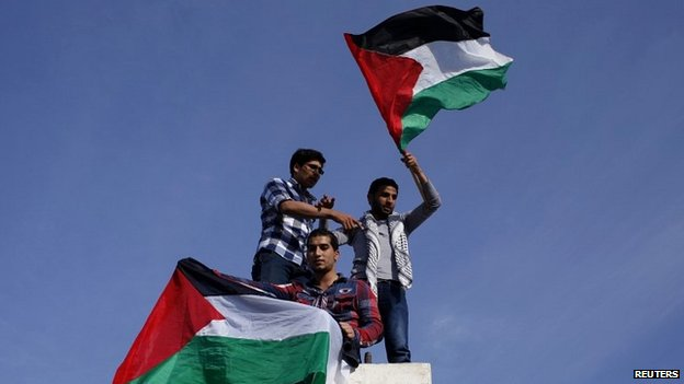 Palestinians hold national flags as they celebrate the reconciliation agreement in Gaza City - 23 April 2014