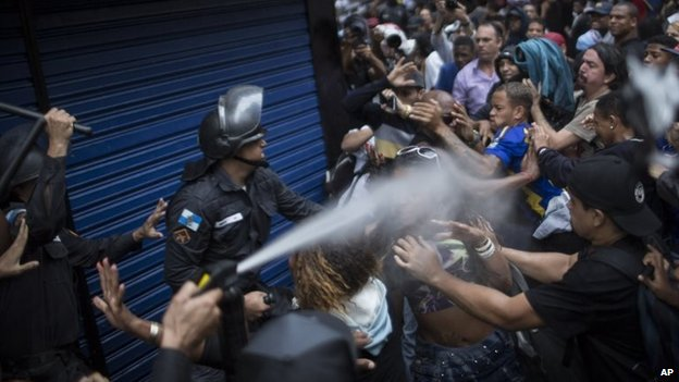 A woman is pepper sprayed by riot police during a protest in Rio de Janeiro, April 24, 2014.