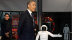 President Obama walks next to robot