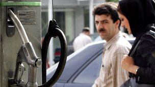 Iranian couple walks past a petrol station in Tehran (archive)