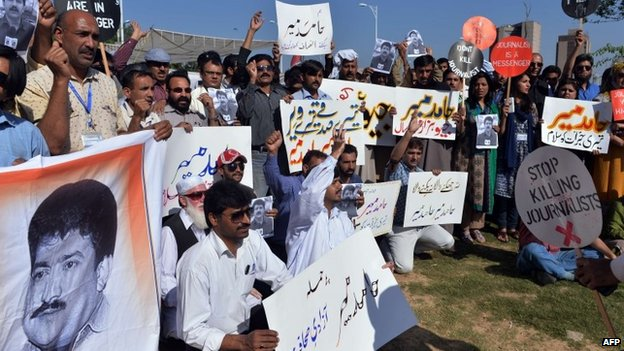 Pakistani journalists hold placards and photographs bearing the image of Geo television journalist Hamid Mir during a protest against the attack on Mir by gunmen in Islamabad on April 23, 2014