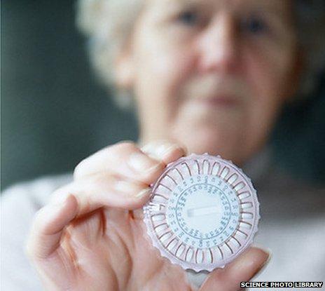An elderly woman holding up a pill dispenser