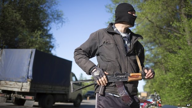A pro-Russian armed man guards a checkpoint near Krasny Liman village outside Sloviansk, Ukraine, 24 April 2014