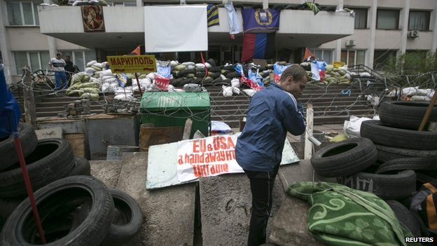 A pro-Russian man stands on barricades outside the Mariupol town hall, East Ukraine, 24 April 2014