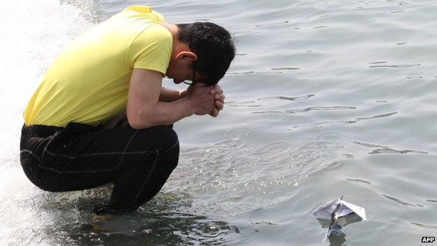 A relative of a passenger aboard the sunken ferry prays after releasing a paper boat in honour of those missing or killed