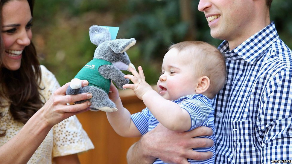 Prince George pictured at Sydney Zoo playing with a toy.