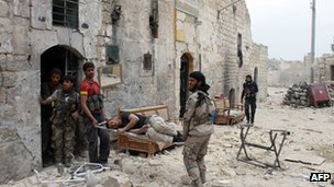 An injured rebel fighter is helped by his comrades in Aleppo