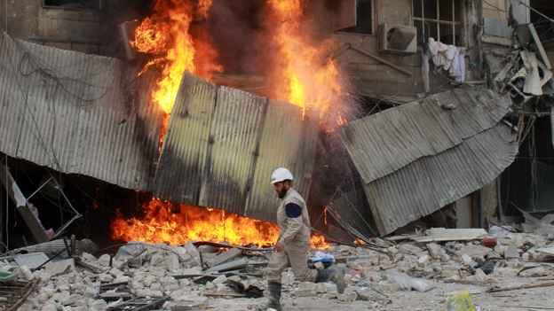 A man runs past the scene of an explosion in Aleppo