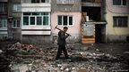 A man passes the remains of a house demolished by a bulldozer in a Roma suburb in the Bulgarian city of Plovdiv