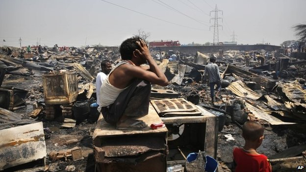 An Indian man wails as he sits amidst the remains of his home after a fire in a slum in New Delhi, India, Friday, April 25, 2014.