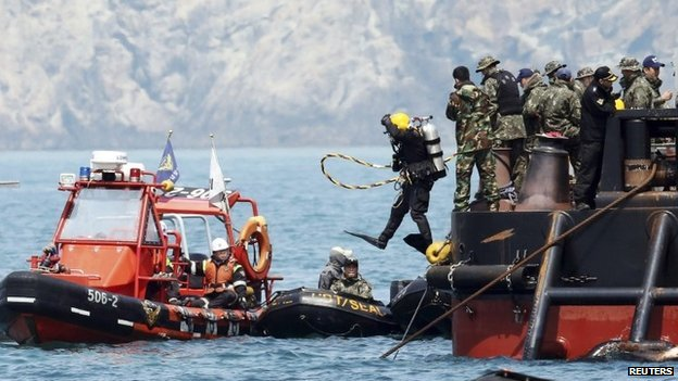 A diver jumps into the sea above the capsized passenger ship in Jindo - 25 April 2014