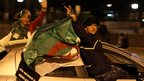 Algerians hanging out of a car waving a national flag, Algiers, Algeria - Friday 18 April 2014