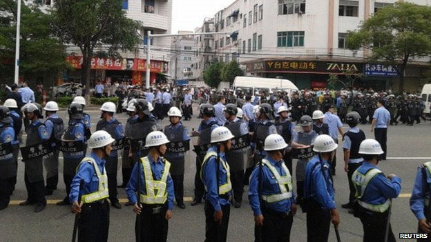 Policemen are seen on patrol as workers go on strike outside a Yue Yuen factory in Dongguan, Guangdong province, 15 April 2014