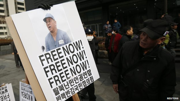 Anti-North Korean protesters hold a sign showing US Christian missionary Kenneth Bae in central Seoul on 16 February 2014.