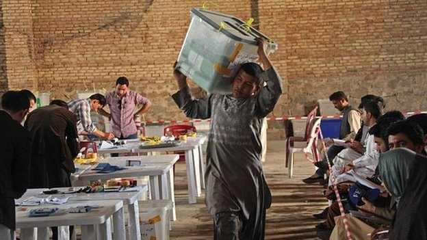 A worker for the Afghan election commission office unloads ballot boxes in Herat Province (20 April 2014)