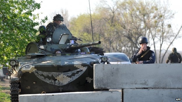 Ukrainian policeman and soldiers in a tank guard at a checkpoint near the eastern city of Sloviansk. Photo: 25 April 2014