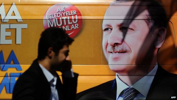 A Turkish man talks on the phone as he walks in front of a poster displaying a portrait of Turkish prime minister Recep Tayyip Erdogan i