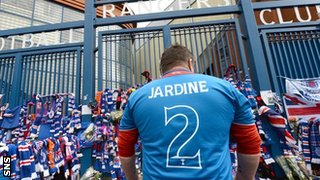 A fan pays tribute to Rangers great Sandy Jardine, who died on Thursday