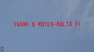 A plane flys over Old Trafford with a 'Thank you Moyes' banner