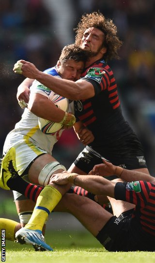 Damien Chouly of Clermont Auvergne is tackled by Jacques Burger