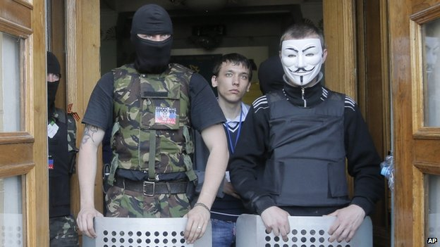 Masked pro-Russian activists guard the entrance during their mass storming of a regional TV centre in Donetsk