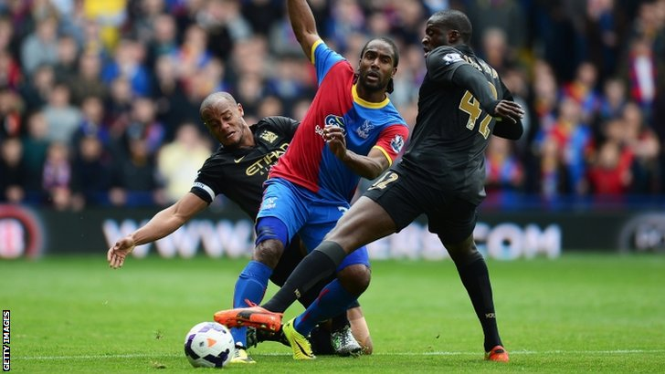 Cameron Jerome of Crystal Palace is tackled by Vincent Kompany