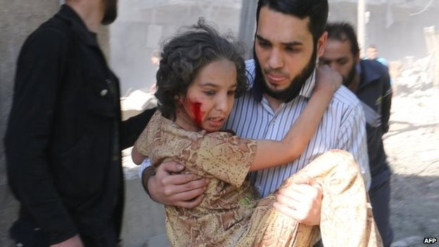 "A man carries a wounded girl following a reported regime bombardment with explosive-packed ""barrel bombs in Aleppo"
