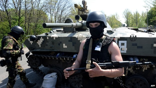 A Ukrainian soldier stands by an amoured personnel carriers at a check-point about 25 km from Sloviansk