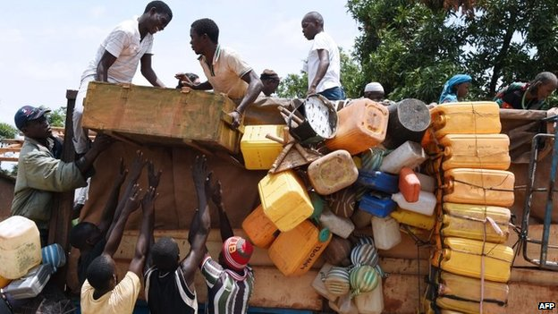 People stand atop a vehicle loaded with people and goods in the PK-12 district of Bangui