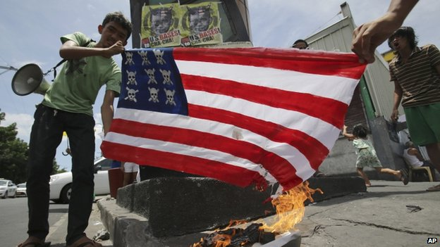 Filipino activists burn a mock US flag as they hold a short protest in Manila, Philippines on Sunday 27 April 2014