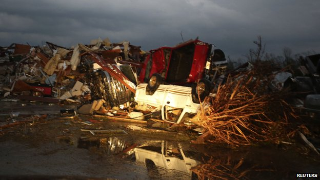A flipped pickup truck is reflected in water after a tornado destroyed the town of Mayflower, Arkansas on 27 April
