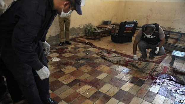 Pakistani forensic experts collect evidence at a religious seminary after a bomb attack in Karachi on April 28, 2014.