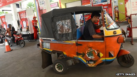 A bajaj fills up at a state-owned petrol station in Jakarta