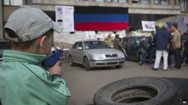 A boy points a toy gun as a group of journalists stand in front of Sloviansk's town hall (28 April 2014)