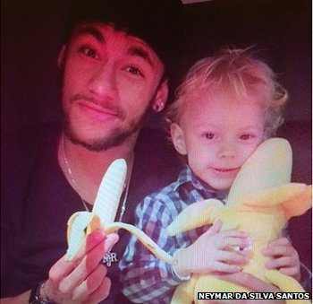 Neymar, side by side with his son, holding a banana